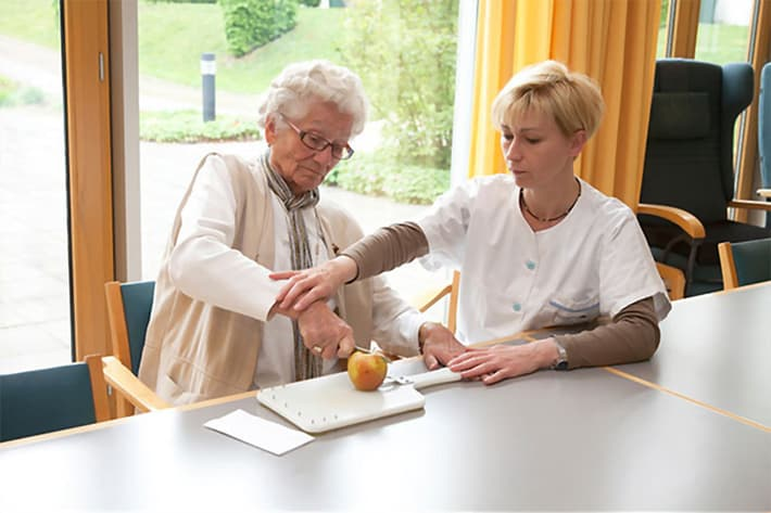 geriatric nurse helps a stroke patient