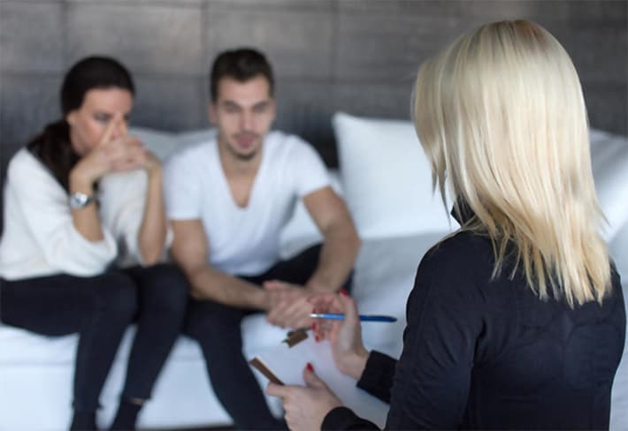 Therapist woman talking with young sad couple